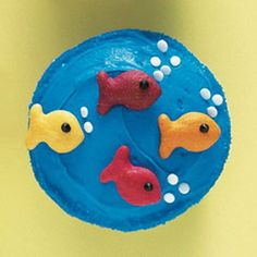 Fishies in the Sea Frost cupcake with blue frosting. Attach colored Goldfish crackers to the cupcake. Use chocolate frosting to pipe eyes on fish. Add white candy confetti for bubbles.