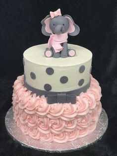 Pink buttercream rosettes with gray fondant polka dots elephant themed baby shower cake.