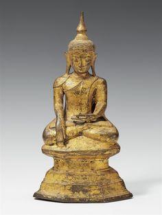 A Burmese gilt bronze figure of Buddha Shakyamuni. 18th/19th century A Burmese gilt bronze figure of Buddha Shakyamuni seated in meditation (padmasana) on a stepped base, the right hand in bhumisparsha mudra, the left hand in dhyana mudra above the feet. 18th/19th century. Height 33.5 cm