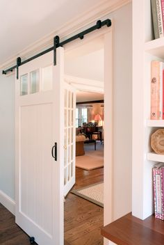 Barn door with window separating kitchen from living areas