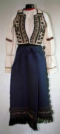 Romanian Women's costume,county of Sibiu, zone Rupea; Gathered neck chemise (Cămaşă cu mâneca din gât) with wide frills (fodor) just below the elbow. wide horizontal band of geometric red and black embroidery above the elbow, this style of decoration being known as cămaşă cu şire peste cot, and a row of black silk embroidery on the frill and on the sleeve ends.  A wide row of white crochet lace at the wrists. Vest (pieptar) with black, dark blue and green embroidery, and edged in black…