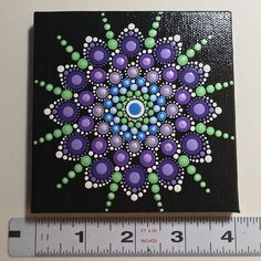 """Hand painted with acrylic in Blue, Green, and Purple. Sprayed with a high gloss sealer to protect the colors. Canvas size is 4"""" X 4""""."""
