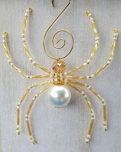 Handmade beaded spider ornament, made with a gold iridescent faceted glass head bead, a large created pearl body bead, and coordinating leg beads. This ornament measures approximately 4 inches and comes with a matching hook and the Christmas Spider Legend. Spiders are an ancient symbol of