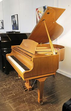 A Carlmann baby grand piano with a walnut case and spade legs at Besbrode Pianos. A great value baby grand at £3500