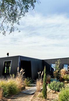 An eco-friendly home in the Barrabool Hills with passive design principles, In the hills behind Victoria's Surf Coast. A black colourbond steel exterior forms a dramatic silhouette in the countryside.