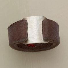 "Leather this supple is a rare find. Ours loops through both sides of a rectangular tab of hammered sterling and joins with three tiny red stitches beneath the finger. Handcrafted in USA by Renee Garvey. Whole sizes 5 to 9. 3/8""W."