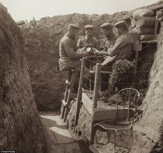 WWI picture of German soldiers playing cards together next to their trenches 'garden'