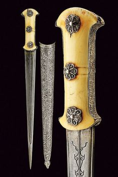 Ottoman hancer / court dagger, first quarter of the 19th century. Straight, double-edged blade of fine damask, engraved with floral motifs and bas-relieved raisers. Walrus-ivory grip scales (small missing parts), birth silver band and rosettes at the center. Wooden scabbard with silver-inlaid covering, finely embossed with floral motifs, length 43.7 cm.