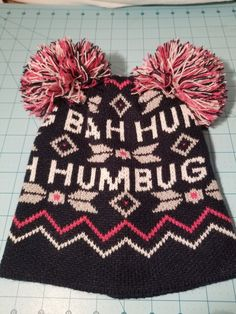 4aeb64d1e Bah humbug Beanie dark blue pink grey and white with two pom poms on top.