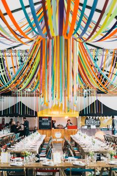 Multicoloured ribbon canopy by Andy Tomlinson and street food stalls all set up at our London warehouse wedding back in May. Liz LInkleter Event Planning & Design. Photo Robbins Photographic