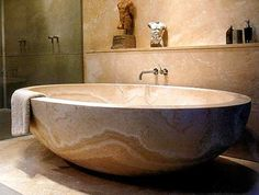The bathtub, which is hewn from a single rock of marble, was made extra-large for Ross after an initial version was deemed to be too small. Description from dailymail.co.uk. I searched for this on bing.com/images