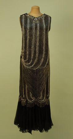 ART DECO BEADED BLACK SILK GEORGETTE GOWN, 1920's. Sleeveless column with V-neck and back in a chevron and stripe swag pattern of crystal, white and rhinestone beading with banded neckline and right hip medallions, looped scalloped fringe below knee over a gathered chiffon flounce, hook & eye closures on both shoulders.
