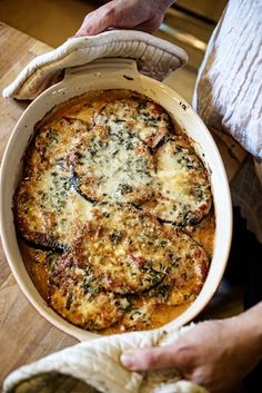 Eggplant Gratin with Herbs and Creme Fraiche    2 medium to large eggplant, sliced 1/2″ thick    salt & pepper    olive oil    1 quart simple tomato sauce    3 Tbs. minced chives    3 Tbs. minced parsley    1 Tbs. thyme leaves    12 oz. creme fraiche or heavy cream    4 oz parmesan cheese, grated