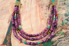 Beautiful Necklace featuring Genuine Sugilite with accents of Turquoise, Blue Lapis, Tiger's Eye, Black Onyx and Picture Jasper. Sterling Silver and Gold Fill Barrels. Created by Navajo Artist Tommy Singer.