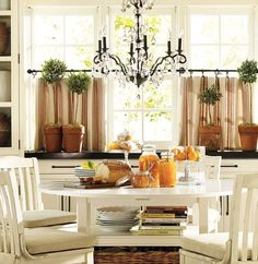 These cafe curtains are an essential for a bright kitchen like this one. The beige looks really nice when paired with the green plants. The cafe curtains block out enough light that it won't blind you while you're eating but still lets you enjoy natural lighting.