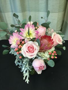 Romantic meets unique in this lush and textural bouquet. Hydrangea, roses, dahlias, and proteas, hypericum berries, dusty miller, and silver dollar eucalyptus.