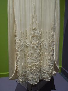Her silk gown has faux pearls, some of them clustered and surrounded by beads.