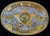 "Oregon State Police 60th Anniversary Belt Buckle - 1991. The buckle is plated in 24 karat gold and manufactured by Creative Casting. It measures 3 3/4"" wide by 2 3/4 tall. The buckle will fit up to a 2"" wide belt and comes with the original paperwork. This is an amazing find for the person who collects police memorbilia and especially Oregon police memorbilia."