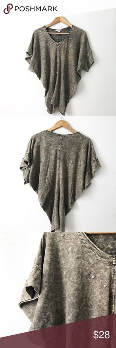 Romeo & Juliet couture  acid wash dolman top Beautiful dolman top in gray acid wash with metal circled details . Some of these metal circles are missing but it is not noticeable .  Wide arm holes. Top is smaller at bottom hem  and wider at top. So stylish and versatile . Perfect with some ripped jeans shorts ! Measurements : length : 26 1/4 in.   Pit to pit : 31 in.    Arm hole : 12 in. Romeo & Juliet Couture Tops Tunics