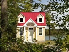<p>This darling red-roofed cottage sits in a grove of leafy trees near the water's edge in Freeport,... - Courtesy of Creative Cottages/Trent Bell