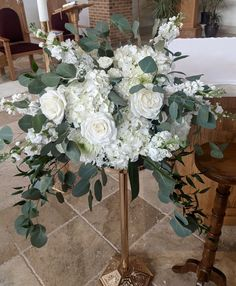 Altar arrangement for wedding ceremony with white flowers and eucalyptus greenery.