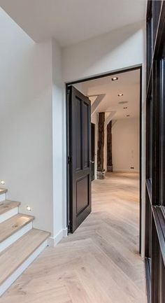 High black doors with beautiful parquet flooring laid on the tra . High black doors with beautiful parquet flooring laid on the stairs. Style At Home, Stairs Colours, Floor Colors, Dark Doors, Interior Stairs, Interior Doors, Parquet Flooring, Dark Flooring, Wood Doors