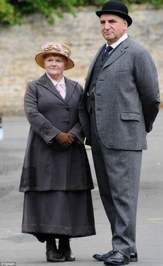Standing tall: Jim Carter who plays Carson, Lesley Nicol (Mrs Pattmore) were seen in costume in the village