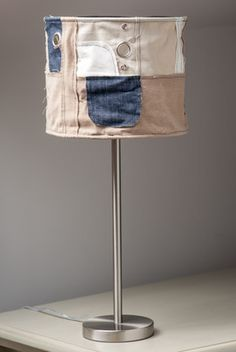 Contemporary Squashed Look Table Lamp Chilled & Relaxed...  Different and attractive table lamp that will definitely catch the eye. Perfect for the 'lads' room, children's playroom or where a more relaxed look is required. The metal base is teamed with a denim blue, cream, beige and white shade that's been squished to perfection - something that's all the rage right now.