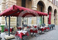 Outdoor restaurant in the historical part of the old town of Bassano del Grappa and historical buildings in Veneto, Italy.