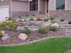 jardinet devant la maison aménagé avec une fontaine, des arbustes vivaces et des fleurs