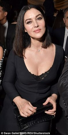 In the frow: Monica refused to blend into the monochrome background as she sat front row a...