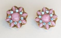 Vintage Rose Pink Plastic Lucite and Blue Rhinestone Flower Shaped Post Earring. The flower sits on an open work gold tone findings.  1 1/4 in diameters. 1 thick including the post. Very good condition. We are very careful with our photographs and description of the colors in each piece of jewelry. Colors can be vary from one computer screen to another.  Our shipping prices are estimates. We will refund the difference in shipping cost if the estimate shipping is $2 or more over the actu...