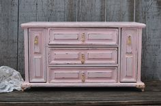 Upcycled vintage jewelry and music box. Wood, hand painted in soft pink, lightly distressed, and finally hand waxed. There are 3 drawers and 2 drop down ring holders. The music box plays a waltz when