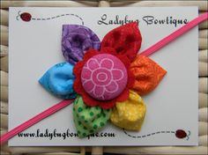 """Such a sweet and simple little flower for any age!  The flower is made with cotton fabric and measures approximately 2.5 inches across. It is topped with a matching fabric button.  It will be attached to a 1/8"""" skinny elastic headband in the size of your choice, or an alligator clip that has ..."""