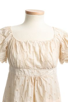 Sprigged cotton dress, with an overall eyelet design and an elaborate scalloped hem border. From the collections of the Charleston Museum
