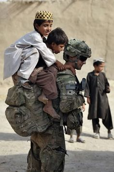 US soldier Specialist Collin Rand from the Charlie Company, 2-87 Infantry, 3rd Brigade Combat Team plays with Afghan children during a joint patrol with Afghan National Army soldiers at Kandalay village in the southern Afghan province of Kandahar on August 8, 2011