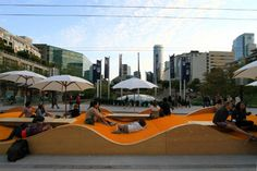 Picnurbia, Vancouver 2011. The temporary landscaping project aims to address shortage of decent public spots for urbanites to gather, relax and picnic. Picnurbia consists of a 28 meters long and 4 meters wide 'uber-picnic-blanket' comprised of an undulating wooden structure covered with yellow artificial lawn.