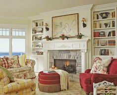Such an inviting and cozy living room - vibrant colors and pretty patterns, yet subtle, calming with soft textures - love the books, fireplace, large window, round foot rest or table?