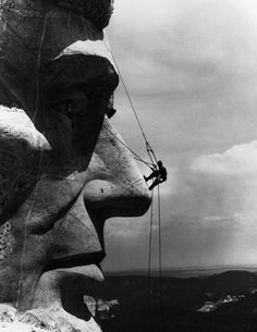 A repairman on Abraham Lincoln's face from Mount Rushmore National Memorial (1962)