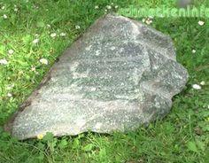 Ein grün glänzender Stein ergänzt die Beplanzung des Kübels