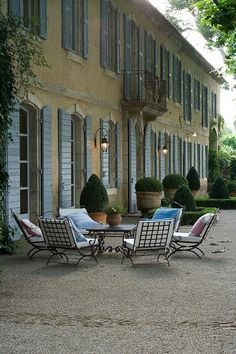 white upholstered cushions on wrought iron with potted boxwoods