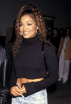 Janet Jackson 90s outfit: black crop top and high waisted jeans.