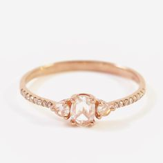 """14K. Rose Gold Triple Diamond Ring / Liven, $1,000 -- """"The centerpiece of this lovely ring is a 3 millimeter by 4 millimeter rose-cut white diamond, framed on either side by a 2 millimeter round white diamond (for a total of .19 carats). The prong setting is so delicate that the stones appear to float atop the blushing 14 karat rose gold band, which is inset halfway around with 16 pavé white diamonds."""""""