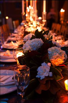 """We loved the mix of romantic magnolia """"runners"""" with modern glass candelabras."""