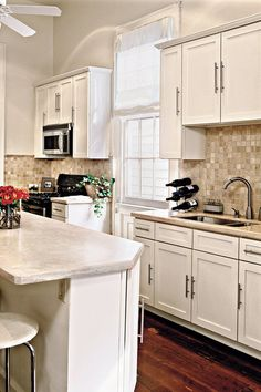 A white shade allows light to stream into the small but efficient cooking space. In the cooking area, cream-colored countertops and tiles blend beautifully with the white cabinetry. Open space above the cabinets increases the sense of height. Metal hardware on cabinets adds a punch that is repeated on the stainless steel refrigerator and stove.