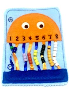 Orange jellyfish bead counting page quiet book page. Touching and colors help children to learn to count. Kids can feel, touch, and learn colors while learning to count to eight. All of our pages can be combined to create the perfect quiet book or buy just this page for hours of fun. All of the pages have 2 holes on th