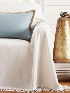There's nothing easier than tossing a sheet of fabric over a sofa than pinning and tucking it into shape. But you can give it a little extra moxie by using a fringed blanket, oversize shawl or other cover with fun trim.