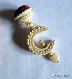 Carved Ivory sewing clamp, English cir 1810. Beautiful carving of tiny flowers cover this elegant sewing clamp. Used to clamp your fabric to the table top. The top of the clamp holds the pins. Once clamped, you have hands free to cut the fabric.  5ins