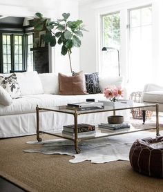 A black and white cowhide rug is layered atop a bound sisal rug in this stunning living room featuring a brass and glass rolling coffee table positioned in front of a white slipcovered sofa accented with assorted black, white, and brown pillows and placed in front of a fiddle leaf fig.