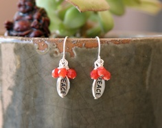 """These handmade earrings were created using coral orange crystals, silver plated peace charms, and 925 sterling silver french earring hooks.  The earrings are approximately 1"""" in length including the 925 sterling silver french earring hooks.  $15.00"""